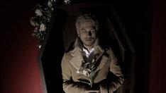 写真は新曲「アイシテル」ビデオクリップより。花を抱え棺おけに横たわる平井堅。