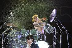 ドラムを叩きながら激しく水をまき散らすYOSHIKI。手前はToshI。
