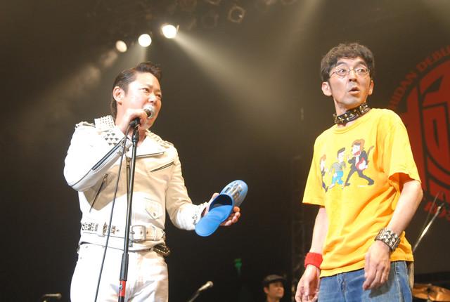 ショートコント「1!2!3!4!」の前振りとして与太話をするバイト君(写真右)と、虎視眈々とスリッパを打ち下ろすタイミングを狙う破壊(写真左)。