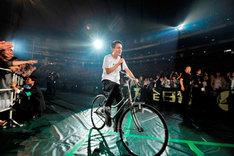 客席エリアを自転車で快走しながら「キラキラ」を歌う小田和正。(撮影:菊地英二)