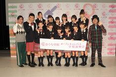 写真は囲み取材の様子。倉本美津留校長(写真右端)、メンバーと同じ衣装で体験入学した小島よしお(写真左から2番目)も一緒に記念撮影。