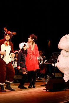 写真は「飯舘村卒業式イベント」の様子。トナカイに扮した伊勢谷友介(写真左)とクリスマスカラーの衣装で登場した岡本真夜(中央)。