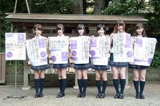 乃木神社境内に設置されるポスターを手に記念撮影する乃木坂46七福神の6名(風邪で欠席の星野みなみを除く)。