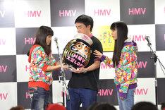 以前メンバーが目を入れただるまにサインを書く百田夏菜子。なお、だるまがかぶっているのはももクロオフィシャルファンクラブ「ANGEL EYES」入会特典のベレー帽。