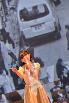 渋谷の街を映したムービーをバックに歌う武藤彩未。