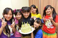 バックヤードでメンバー特製ケーキを持つ根岸可蓮とそれを囲むメンバー。