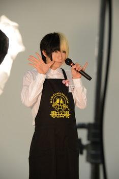 「カラオケルーム歌広場」のユニフォームを着用し、ポーズを決める歌広場淳。