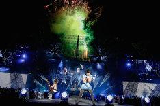 ライブの終盤で、花火をバックに熱演を繰り広げるONE OK ROCK。