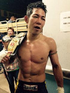 チャンピオンベルトを手にする竹村哲。