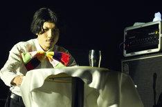 テーブルクロス引きに挑戦する安西卓丸(B, Vo)。(撮影:中島未来)