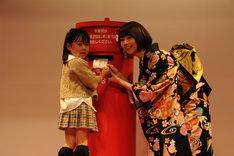 子供の年賀状投函をサポートする橋本奈々未(右)。