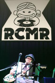 「RCMR(ラーメンカレーミュージックレコード)」のロゴをバックに歌う奥田民生。(撮影:山本倫子)
