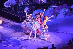 世界地図が描かれたステージの上で歌うでんぱ組.inc。