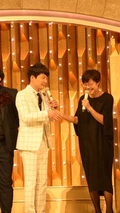 握手を交わす星野源(左)と総合司会の有働由美子アナウンサー(右)。