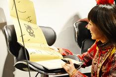 ツアーパンフレットにサインを書き込む百田夏菜子。