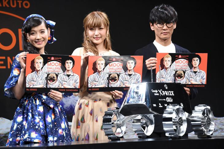 「宇宙兄弟」と「au×HAKUTO MOON CHALLENGE」のコラボビジュアルが描かれたパネルを手にする、左から篠原ともえ、神田沙也加、山口一郎(サカナクション)。