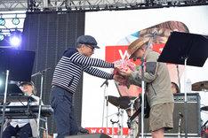 鈴木慶一に花を贈る高橋幸宏(左)と、受け取る鈴木慶一(右)。(Photo by TEAM LIGHTSOME)