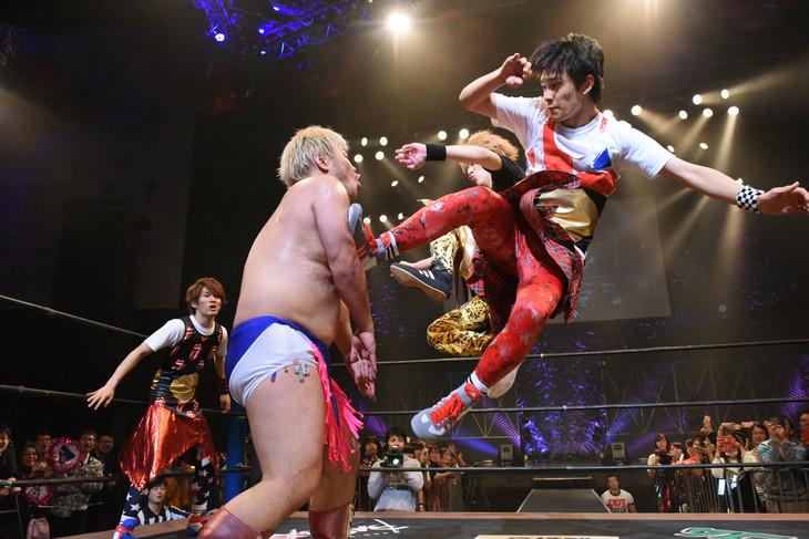 男色ディーノ(左)にダブルのドロップキックを仕掛けるDISH//のTAKUMI(右手前)とRYUJI(右奥)。(写真提供:DDTプロレスリング)