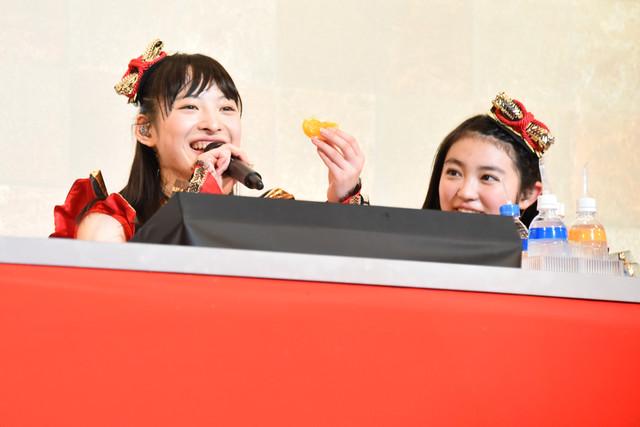 ステージ上でみかんをモリモリ食べる松野莉奈(左)。