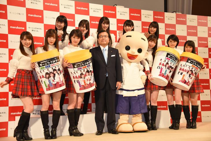 マルコメ新商品発表会の様子。青木時男マルコメ代表取締役(前列左から4番目)、マルコメ君(前列右からから4番目)と記念撮影するモーニング娘。'17。