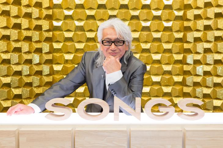「SONGS」のロゴを前に微笑む玉置浩二。(写真提供:NHK)