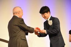 橋本隆氏からトロフィーを受け取る星野源(右)。