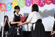 吉井和代さん(右)から花束を受け取る西野七瀬(左)。