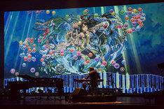「パズル&ドラゴンズ」とコラボしたピアノプロジェクションと共に「KARIN」を演奏するまらしぃ。(撮影:石阪大輔)(撮影:石阪大輔)