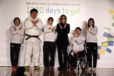 XポーズをするYOSHIKI(X JAPAN)とパラスポーツ選手たち。