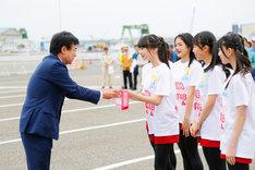 新潟商工会議所の福田勝之会頭からたすきを受け取るNGT48のメンバーたち。