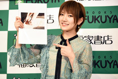 1st写真集「飾らない宝石」のお気に入りカットを指差す岡田奈々。