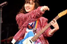 ギターを弾きながら歌う鈴木愛理。