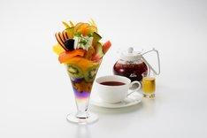 """京橋千疋屋フルーツパーラーで提供される「""""八月の夢""""福耳レインボーフルーツパフェ」とドリンクのセット。"""