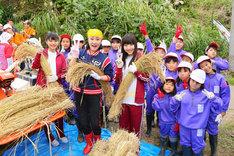 「小林幸子田」で小林幸子や地元の小学生と脱穀を行った本間日陽、日下部愛菜。(c)AKS