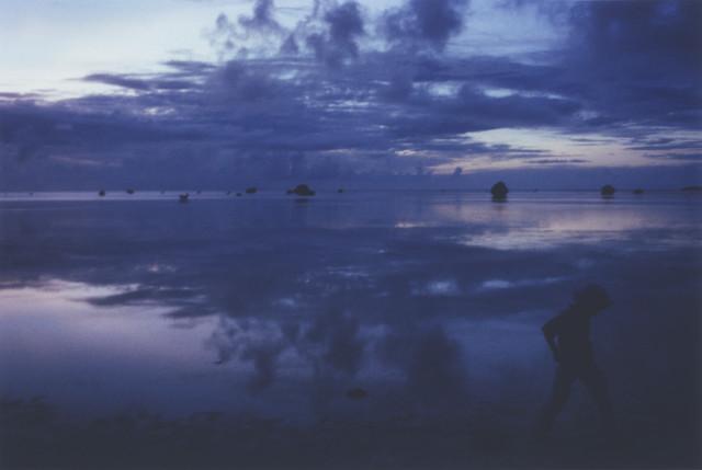 写真展「DEAR」より。空と波だけを写した作品郡の中で唯一、風景全景を写した。右下のシルエットは撮影旅行を共にした息子。2016年撮影。(写真提供:アミタマリ)