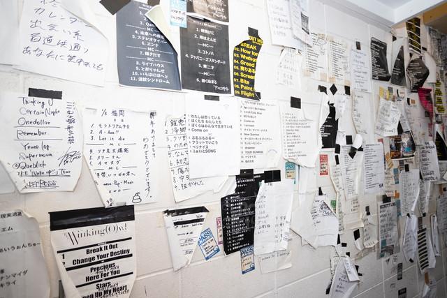 楽屋の壁にはこれまで出演したバンドのセットリストやバックステージパスが無数に貼られている。