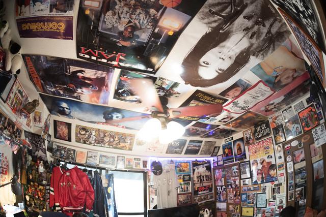 SITEの部屋の写真。天井までほとんど隙間なくポスターが貼られている。