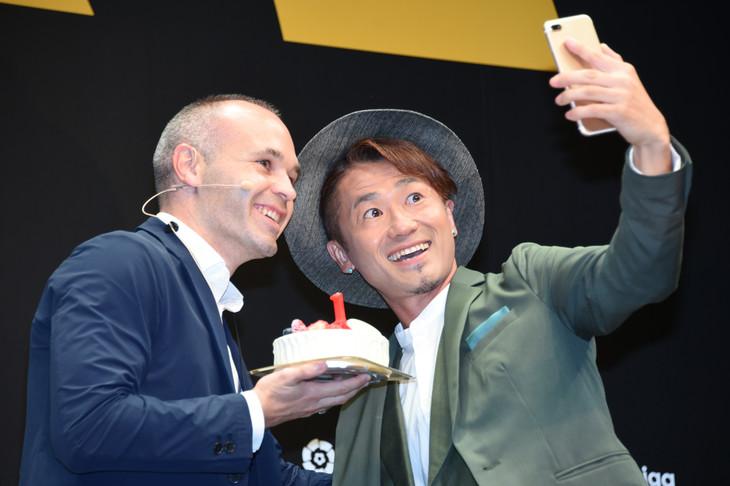 アンドレス・イニエスタ(左)とセルフィーを撮るナオト・インティライミ(右)。イニエスタが手にしているのはJリーグデビュー1周年をお祝いするケーキ。