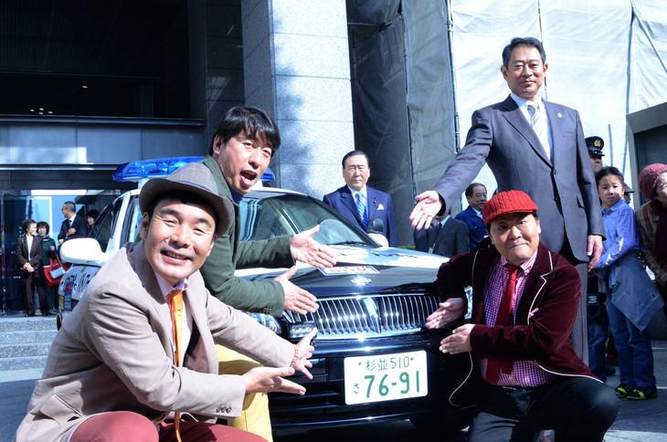 杉並ナンバーを装着した安全パトロール車とのフォトセッションに応じる、ダチョウ倶楽部と田中良杉並区長。