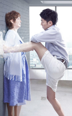 熟女に脚で壁ドンする綾部(右)。
