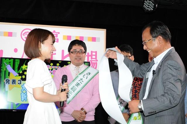 さいたま市経済支局長・岡安博文氏(右)より「さいたま観光大使」のたすきを授与される山田菜々(左)。