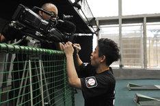 撮影中のテレビカメラのレンズにサインを書くスピードワゴン井戸田。