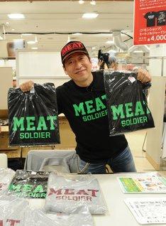 自身がプロデュースした「MEAT SOLDIER(ミートソルジャー)Tシャツ」を掲げる寺門ジモン。