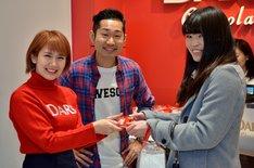 ファンにDARSを手渡す岡井千聖(左)、さわやか五郎(中央)。