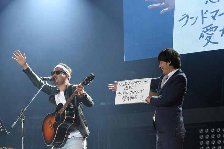 上々軍団。「ランドマークタワーで秘密のデート」を歌唱するさわやか五郎(左)と歌詞カードをめくる鈴木(右)。(写真提供:アップフロント)