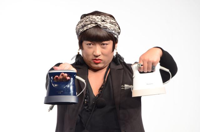 衣類スチーマーを持ってポーズを決めるYOKO FUCHIGAMI。