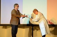 京都造形芸術大学の本間正人副学長(左)から委任状を受け取る水道橋博士(右)。