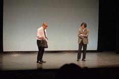 マツモトクラブ(右)が舞台に忘れていったカバンを拾うルシファー吉岡(左)。
