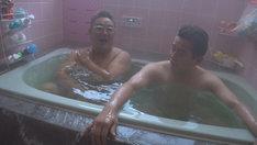 但馬牛の牧畜を営む家庭の風呂に浸かるサンドウィッチマン伊達(左)とスピードワゴン井戸田(右)。(c)NHK