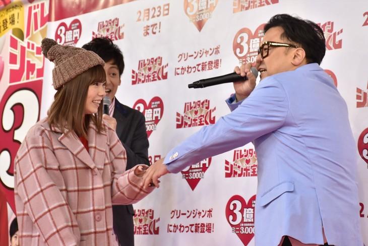 島崎遥香(手前左)とのバレンタインデート権を懸けた告白対決で相方・村田(後方)に勝利したことを、島崎に手を握られたことで知る、とろサーモン久保田(右)。